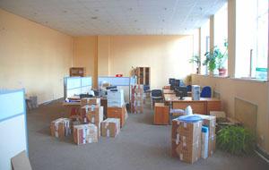 Компьютеры и оргтехника упакованные грузчиками в коробки перед офисным переездом